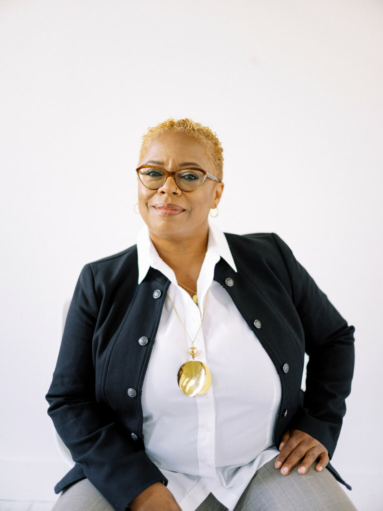 Kawania Wooten in a professional photo. She has blonde hair, brown glasses, a gold necklace, white dress shirt and black jacket. The Enlightened Creative.